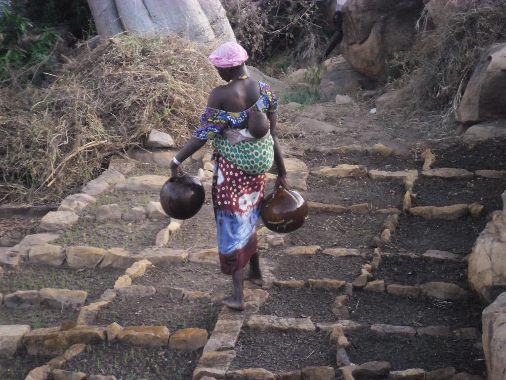 femme portant un bébé et deux jarres